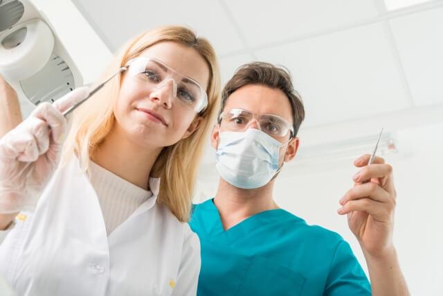 抜歯手術で口を覗く歯科医