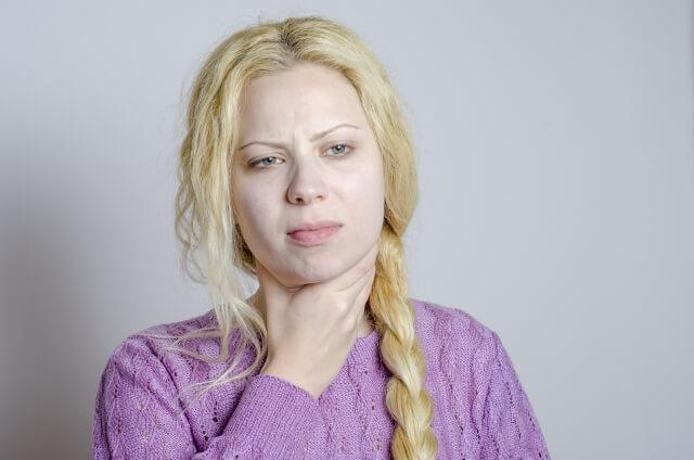 喉に痛みを感じている女性