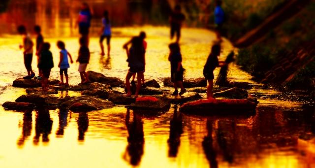 川べりで遊ぶ子供たち