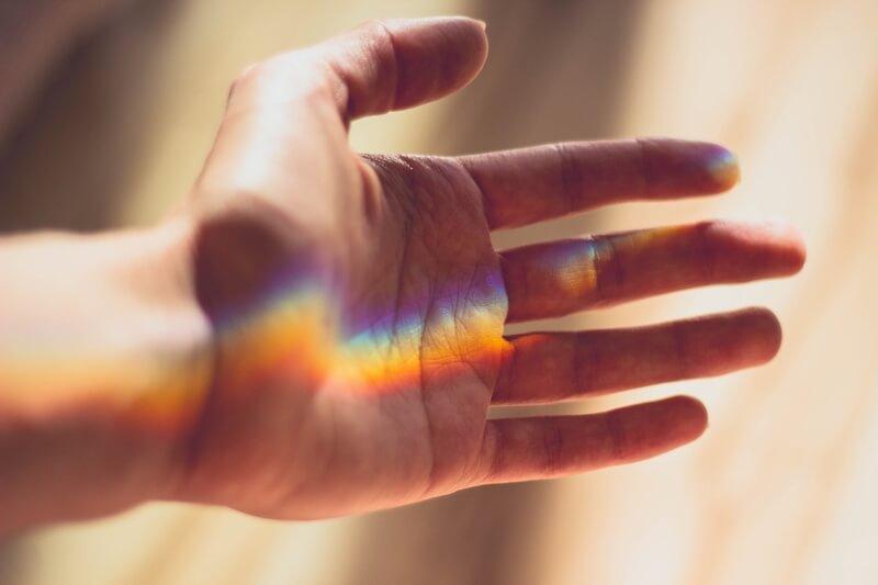 虹色の光が差し込む手